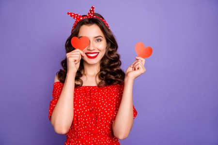 La bella signora che nasconde l'occhio con le piccole carte di figura del cuore indossa il fondo viola isolato vestito rosso