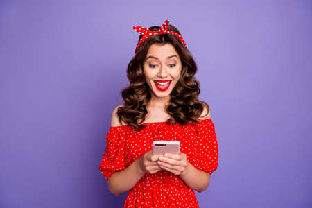 Pretty lady holding telephone hands open mouth from cool news wear old-fashioned dress isolated purple background Фото со стока