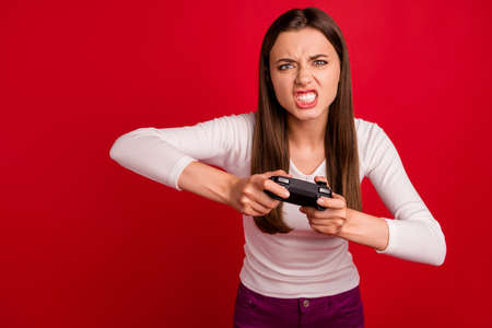 Photo of furious woman out of control losing video game while isolated with red background