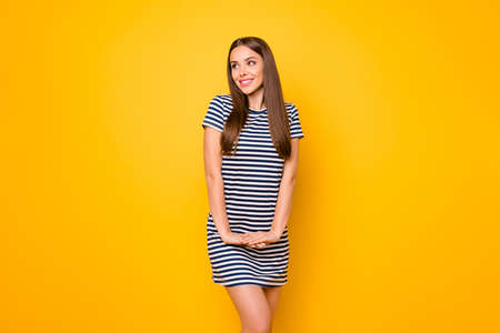 Pretty lady with easy-going mood glad sunny weather wear striped white blue dress isolated yellow background