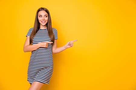 Foto van mooie dame die aangeeft dat vingers lege ruimte dragen, gestreepte witte blauwe jurk geïsoleerde gele achtergrond Stockfoto