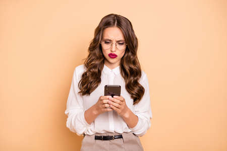 Close-up portrait of her she nice-looking attractive lovely pretty chic gorgeous gloomy moody grumpy disappointed wavy-haired lady reading bad news dislike isolated over beige pastel background