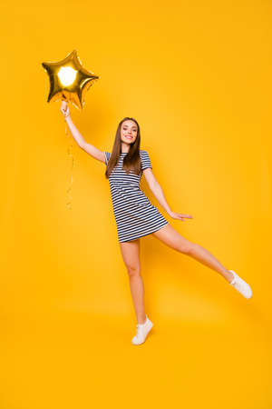 Vertical photo of nice girl play with big star shaped air ballon wear striped white blue dress isolated yellow background