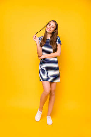 Vertical photo of nice girl glad sunny day wear striped white blue dress isolated yellow background Stock Photo