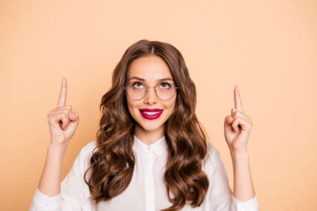 Close-up portrait of her she nice-looking attractive lovely glamorous gorgeous confident cheerful cheery wavy-haired lady pointing two forefingers up ad advert isolated over beige pastel background