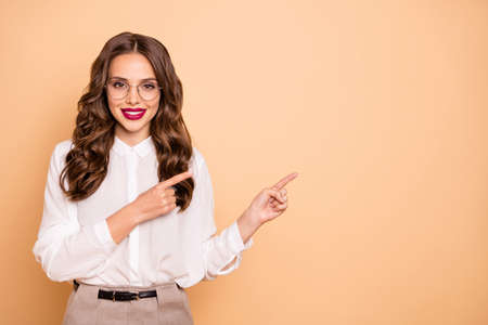 Portrait of her she nice-looking attractive lovely gorgeous cheerful cheery confident wavy-haired lady pointing two forefingers aside advert ad new novelty product isolated over beige background Stok Fotoğraf - 129243983