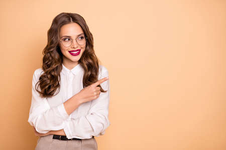 Portrait of her she nice-looking attractive lovely chic glamorous gorgeous cheerful cheery confident content wavy-haired lady pointing aside advert ad copy space isolated over beige background