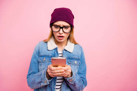 Photo of reading girlfriend wearing eyeglasses having been put in bad mood with received message of her mate while isolated with pastel background