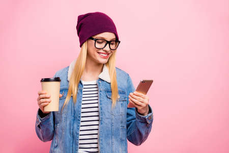 Photo of attractive beautiful girl having coffee break and browsing through her smart phone while isolated with pink background