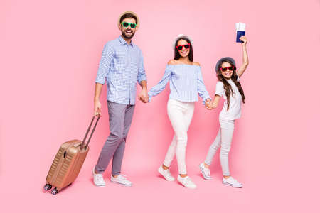 Full length photo of beautiful three people brunettes holding hands trolley wearing t-shirt plaid shirt eyewear headwear eyeglasses isolated over pink background