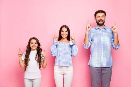 Portrait of lovely parents kid withwavy curly hair wearing white t-shirt checkered plaid shirt blouse pointing at copy space isolated over pink background Zdjęcie Seryjne