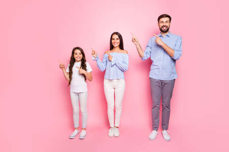 Full body photo of charming family with long wavy curly haircut pointing at copy space wearing checkered shirt trousers pants isolated over pink background Zdjęcie Seryjne