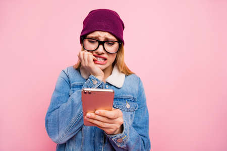 Photo of ashamed afraid pathetic lady receiving angry messages from her parents without ability to send something in return while isolated with pink background Stock fotó
