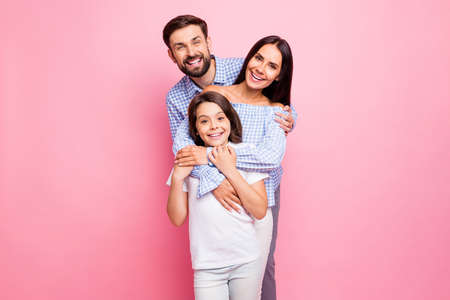 Portrait of cheerful family cuddling smiling wearing checkered plaid shirt off-shoulders white t-shirt isolated over pink background Archivio Fotografico