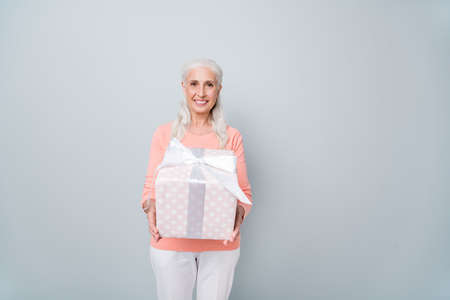 Photo of cheerful nice glad positive old lady giving you large closed box with ribbon and bow on top isolated grey background