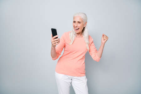 Photo of satisfied cool granny following trends sharing hot posts on social networks isolated grey background