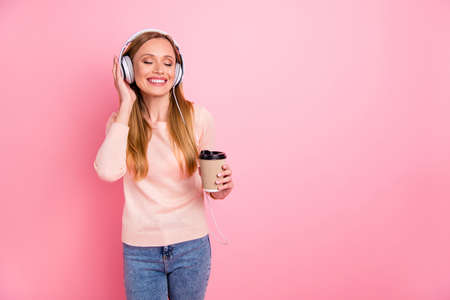 Photo of beautiful lady eyes closed listen favorite playlist earflaps takeout paper coffee wear pastel pullover isolated pink background Stock Photo - 129244066