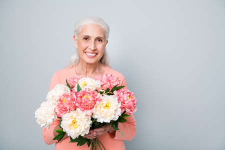 Close up photo of pretty cute sweet kind friendly sincere lady holding nice flowers in hands isolated grey background