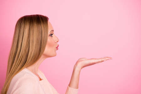 Profile side photo of pretty youth hold hand send air kisses attract husband isolated over pink background
