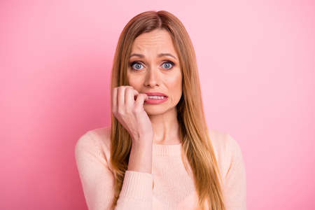 Portrait of disappointed youth teeth bite fingers fail isolated over pink background