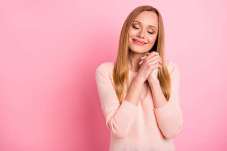 Portrait of cute sweet person hands fists palms close eyes isolated over pink background