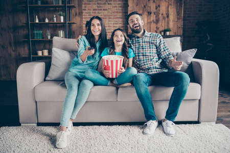 Portrait of cheerful mom dad and little kid have rest laugh look funny film wear, denim jeans checkered shirt t-shirt sit divan in house indoors