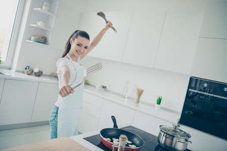 Photo of enjoying loving cheerful glad girlfriend imagining that she is eminent world famous fighter while cooking