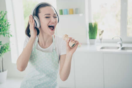 Photo of overjoyed woman imagining some pieces of her kitchenware to be microphones or some other musical equipment