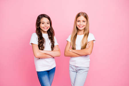 Photo of successful little children girls being photographed over pink background wearing jeans denim with arms crossed