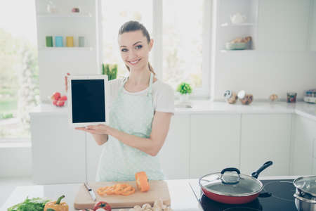 Photo of glad enjoying toothy woman proposing you to purchase tablet and look up recipes via it