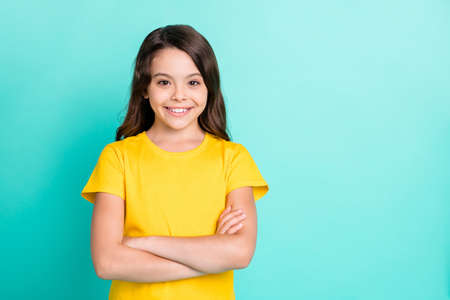 Photo of charming beautiful cute schoolgirl posing in front of camera while isolated with turquoise background