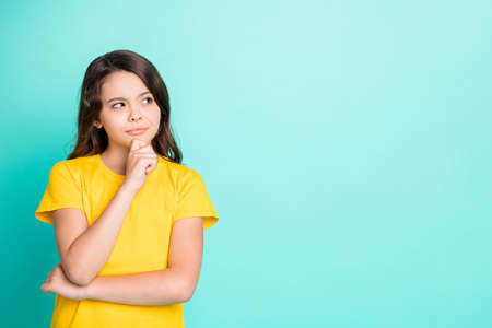 Photo of charming beautiful interested cute girl trying to come up with answer to puzzlement, she has been told while isolated with turquoise background Фото со стока
