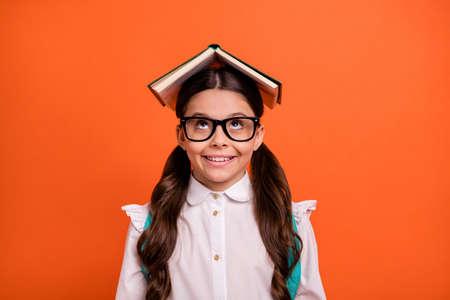 Portrtait of funny funky nice cute kid have printed book head cheerful positive wear white modern blouse eyewear eyeglasses tails bag backpack rucksack isolated orange background Stockfoto