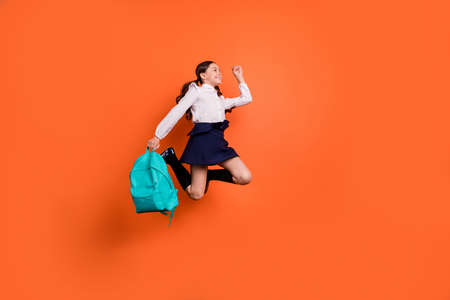 Full length body size profile side view photo cute sweet kid rejoice movement dreamy lesson break pause dress white blouse she her boots trendy stylish pigtails ponytails isolated orange background