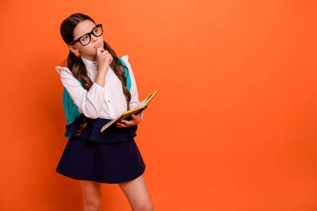 Portrait focused concentrated kid person touch chin she her fingers look have thoughts ask question white blouse shirt modern clothing eyewear eyeglasses ponder dress isolated orange background tails