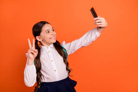 Profile side view photo of positive cheerful cute child make photos video call live v-signs rest relax break pause skirt dress shirt blouse pigtail tails trendy stylish isolated orange background