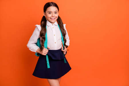 Portrait of lovely nice charming kid touch bag feel satisfied charming dressed blouse white fashionable modern isolated orange background Stock Photo