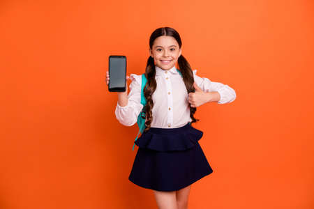 Portrait cute sweet little schoolkid people person have advertisement excellent choice decision backpack bag rucksack skirt dress white blouse shirt dress pigtails ponytails isolated orange background
