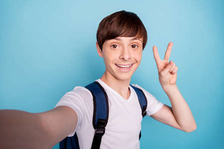 Photo of cheerful rejoicing overjoyed nice boy taking selfie showing v-sign on his way home while isolated with blue background