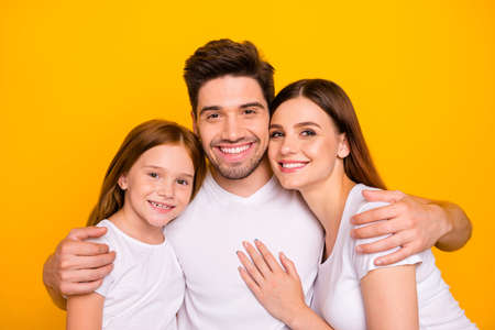 Closeup photo of three family members hugging happy together wear casual outfit isolated yellow background Imagens