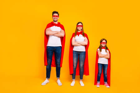 Three family members playing cartoon incredible characters wear superhero cloaks isolated yellow background