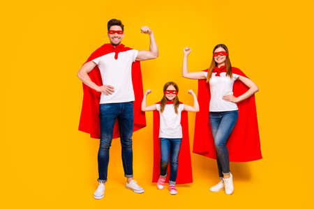 Family of three members playing cartoon incredible characters wear superhero costume isolated yellow background