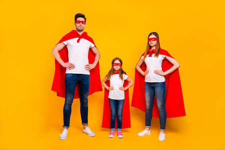 Family spending leisure time playing cartoon characters wear superhero costume isolated yellow background