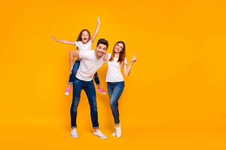 Full length body size view of three nice attractive lovely stylish cheerful cheery optimistic person having fun weekend showing v-sign isolated over bright vivid shine yellow background Фото со стока