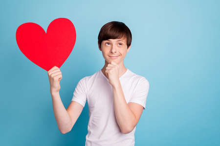 Photo of sly cute boy guessing that who of his lovers will be owner of heart shaped red piece of paper while being isolated with blue background