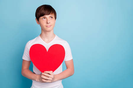 Photo of handsome boyfriend holding red paper heart waiting to be presented to boy girlfriend while isolated with blue background