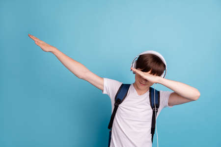 Photo of dancing rejoicing enjoying cheerful boy hiding his eyes behind his hand while isolated with blue background