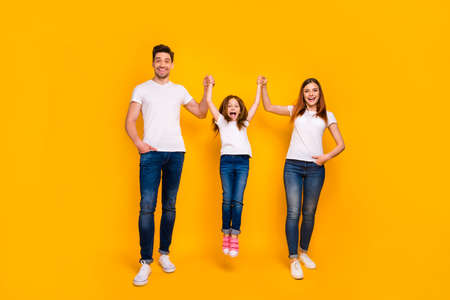 Full length body size view of three nice attractive lovely stylish cheerful cheery carefree person mommy daddy swinging girl having fun life isolated over bright vivid shine yellow background
