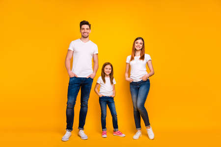 Full length body size view of three nice attractive charming lovely stylish trendy cheerful content person posing holding hands in pockets isolated over bright vivid shine yellow background