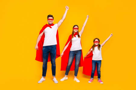 Family members playing cartoon incredible characters protecting world wear superhero flying coats isolated yellow background